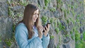 Nätt ung flicka som använder smartphonen Tappningvägg av den lösa stenen i bakgrunden lager videofilmer