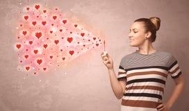 Nätt ung flicka som blåser röda hjärtasymboler Arkivfoton