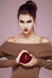 Nätt ung flicka som rymmer det röda äpplet i händer som brutally ser kameran royaltyfri bild