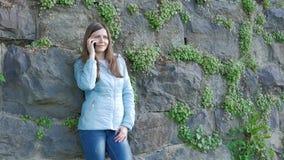 Nätt ung flicka som talar på smartphonen Tappningvägg av den lösa stenen i bakgrunden stock video