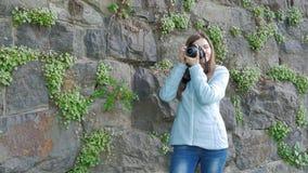Nätt ung flicka som tar foto med en yrkesmässig kamera Tappningvägg av den lösa stenen i bakgrunden stock video