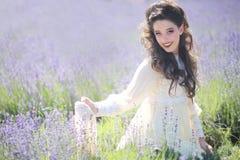 Nätt ung flicka utomhus i ett lavendelblommafält royaltyfria bilder