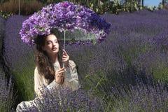 Nätt ung flicka utomhus i ett lavendelblommafält Arkivbild