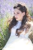 Nätt ung flicka utomhus i ett lavendelblommafält fotografering för bildbyråer