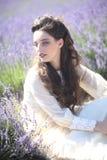 Nätt ung flicka utomhus i ett lavendelblommafält arkivbilder