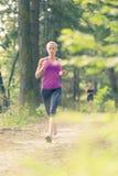 Nätt ung flickalöpare i skogen Royaltyfri Bild