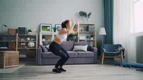 Nätt ung idrottskvinna som hemma gör komplexet av fysiska cardio övningar lager videofilmer