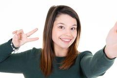 Nätt ung kvinna för fredtecken som gör selfie på vit bakgrund royaltyfria bilder
