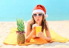 Nätt ung kvinna för julstående i den röda santa hatten med ananas som dricker från fruktsaft för ny frukt för kopp som ligger på  arkivbilder