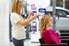 Nätt ung kvinna i hairdress för danande för skönhetsalong och se till spegeln royaltyfria bilder