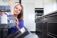 Nätt ung kvinna i hennes moderna och väl utrustade kök Arkivbild