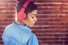 Nätt ung kvinna med hörlurar som tillbaka ser Royaltyfri Bild