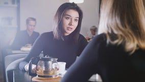 Nätt ung kvinna med svart hår som dricker kaffe och talar med flickvännen i kafét Royaltyfria Foton