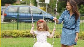 Nätt ung kvinna och hennes liten dotter som rider en gunga på lekplatsen på parkera stock video
