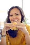 Nätt ung kvinna som äter hamburgaren i kafé Royaltyfria Bilder