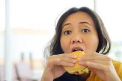 Nätt ung kvinna som äter hamburgaren i kafé Royaltyfri Bild