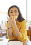 Nätt ung kvinna som äter hamburgaren i kafé Arkivfoto