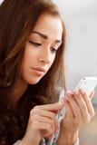 Nätt ung kvinna som använder den mobila telefonen Arkivbild