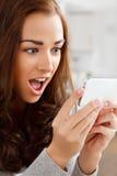 Nätt ung kvinna som använder den mobila telefonen Arkivfoto