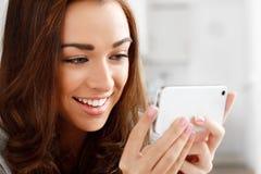 Nätt ung kvinna som använder den mobila telefonen Arkivfoton
