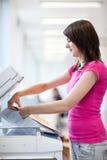 Nätt ung kvinna som använder en kopieringsmaskin Arkivbild