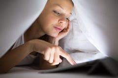 Nätt ung kvinna som använder hennes minnestavladator i säng Arkivfoto