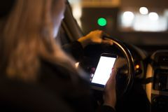 Nätt ung kvinna som använder hennes smarta telefon, medan köra hennes bil på natten arkivfoto