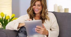 Nätt ung kvinna som använder minnestavladatoren i vardagsrum royaltyfri fotografi