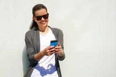 Nätt ung kvinna som använder mobiltelefonen över den vita väggen Royaltyfri Bild