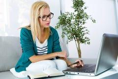 Nätt ung kvinna som arbetar med den hemmastadda bärbara datorn Fotografering för Bildbyråer