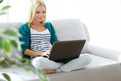 Nätt ung kvinna som arbetar med den hemmastadda bärbara datorn Arkivbild