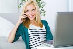 Nätt ung kvinna som arbetar och använder hennes mobiltelefon Arkivfoto