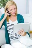Nätt ung kvinna som arbetar och använder hennes mobiltelefon Fotografering för Bildbyråer