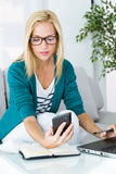 Nätt ung kvinna som arbetar och använder hennes mobiltelefon Royaltyfri Foto