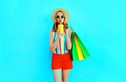 Nätt ung kvinna som dricker fruktsaft som rymmer shoppingpåsar i den färgrika t-skjortan, sommarsugrörhatt, solglasögon, rö fotografering för bildbyråer