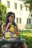 Nätt ung kvinna som dricker ny lemonad i trädgården, produktfotografi för restaurangen, ny lemonad för sommar arkivbild