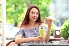Nätt ung kvinna som dricker smoothien royaltyfria foton