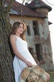 Nätt ung kvinna som framme poserar av lantgården. Mycket attraktiv blond flicka med den vita korta klänningen som rymmer en hatt.  Royaltyfria Bilder
