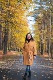 Nätt ung kvinna som går i modern guld- guling för Autumn Park Leaves Fall Relax fritidmode fotografering för bildbyråer