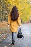 Nätt ung kvinna som går i modern guld- guling för Autumn Park Leaves Fall Relax fritidmode royaltyfri bild
