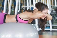 Nätt ung kvinna som gör övning genom att använda övningsbollen arkivfoton