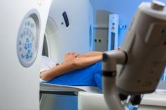 Nätt ung kvinna som goiing till och med CAT Scan för datoriserad axiell Tomography ett medicinskt prov/en undersökning i en moder arkivbild
