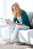 Nätt ung kvinna som hemma använder hennes digitala minnestavla Royaltyfria Bilder