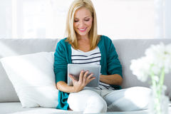 Nätt ung kvinna som hemma använder hennes digitala minnestavla Arkivfoto