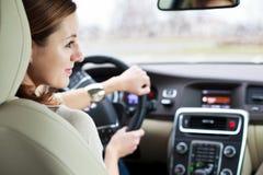 Nätt ung kvinna som kör henne ny bil Arkivbild