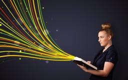 Nätt ung kvinna som läser en bok, medan färgrika linjer är cominen Arkivfoto