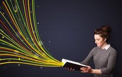 Nätt ung kvinna som läser en bok, medan färgrika linjer är cominen Royaltyfri Fotografi