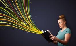 Nätt ung kvinna som läser en bok, medan färgrika linjer är cominen Royaltyfria Bilder