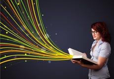 Nätt ung kvinna som läser en bok, medan färgrika linjer är cominen Arkivbild