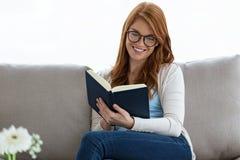 Nätt ung kvinna som läser en bok, medan sitta på soffan hemma Arkivfoto